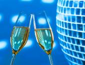 A pair of champagne flutes with golden bubbles make cheers on sparkling blue disco ball background — Stockfoto