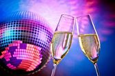 A pair of champagne flutes with golden bubbles make cheers on sparkling blue and violet disco ball background — Stock Photo