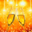 A pair of champagne flutes with golden bubbles on golden stars light background — Stock Photo #52623871