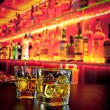 Постер, плакат: Glasses of whiskey with ice on bar table near whiskey bottle on warm atmosphere