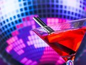 Red cocktail and straw with sparkling disco ball background with space for text — Stock Photo
