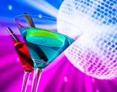 Red and blue cocktail with sparkling disco ball background with space for text — Stock Photo