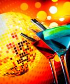 Blue and red cocktail with sparkling disco ball background with space for text selected focus — Stock Photo