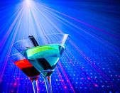 Cocktail with blue light disco background with space for text — Stock Photo