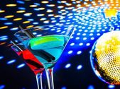 Blue and red cocktail with golden sparkling disco ball background with space for text — Stock Photo