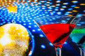 Red cocktail with golden sparkling disco ball background with space for text — Stock Photo