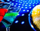 Blue and red cocktail with golden sparkling disco ball background selected focus — Stock Photo
