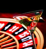 Red dice in the cocktail glass in front of roulette wheel — Stock Photo