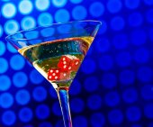 Red dice in the cocktail glass on blue bokeh — Foto de Stock