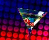 Red dice in the cocktail glass on colorful gradient bokeh — Stock Photo