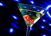 Red dice in the cocktail glass on blue light casino concept — Stock Photo