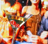 Red dice in the cocktail glass in front of gambling table — Stock Photo