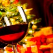 Detail of two red wine glasses against christmas tree background — Stock Photo #57635845