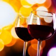 Two red wine glasses against colorful bokeh lights background — Stock Photo #57636849