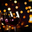 Two red wine glasses on wood table against bokeh lights background — Stock Photo #57654331