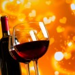 Two red wine glasses against golden hearts bokeh lights background — Stock Photo #57690575