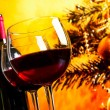 Two red wine glasses near bottle against christmas tree background — Stock Photo #57694063