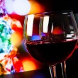Two red wine glasses on wood table against christmas tree light background — Stock Photo #57711913