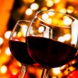 Two red wine glasses against tree of bokeh lights background — Stock Photo #57863761