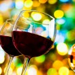 Two red wine glasses against colorful bokeh lights and sparkling disco ball background — Stock Photo #57965529
