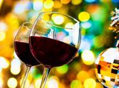 Two red wine glasses against colorful bokeh lights and sparkling disco ball background — Stock Photo