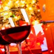 Detail of two red wine glasses against christmas tree background — Stock Photo #58110525