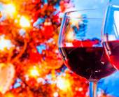 Red wine glass against blur lights tree background — Photo