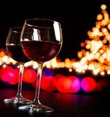 Two red wine glass against bokeh lights tree background — Stockfoto
