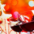 Two red wine glasses against christmas tree background — Stock Photo #58456569