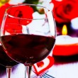 Two red wine glasses on blur hearts and roses decoration background — Stock Photo #58458169