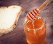 Honey jar on wood table with wooden dipper on top pouring honey — Stock Photo