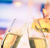 Champagne flutes with golden bubbles on flowers background, wedding and valentine day concept — Stock Photo