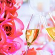 Champagne flutes with golden bubbles on wedding roses flowers background — Stock Photo #60134653