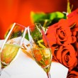 Champagne flutes with golden bubbles on wedding roses flowers background — Stock Photo #60234413