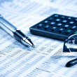 Business fountain pen, calculator and glasses on financial chart — Stock Photo #61527825