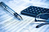 Business fountain pen, calculator and glasses on financial chart  — Stock Photo