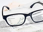 Financial chart and graph of stock indexes see through glasses lens on financial newspaper — Stock Photo