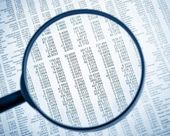 Financial data see through lens of loupe on financial newspaper — Stock Photo