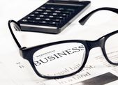 Business word see through glasses lens on financial newspaper near calculator — Stock Photo