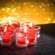 Red burning heart shaped candles on golden hearts bokeh — Stock Photo #63890117
