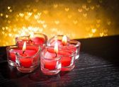 Red burning heart shaped candles on golden hearts bokeh — Stock Photo