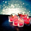 Red burning heart shaped candles on blue hearts bokeh — Stock Photo #63914213