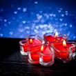 Red burning heart shaped candles on blue hearts bokeh — Stock Photo #63940007
