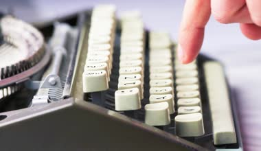 Old typewriter typing. Vintage typewriter being used by male hands seen from the side, using only index fingers pecking keys — Stock Video