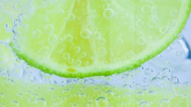Sparkling water with ice and slices lime on white background — Stock Video