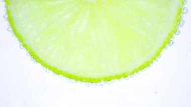 Sparkling water in the glass with bubbles and lime slice on white — Stockvideo
