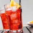 Glasses of spritz aperitif aperol cocktail with orange slices and ice cubes near plate of slices oranges — Stock Photo #72963167