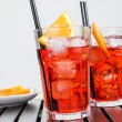 Glasses of spritz aperitif aperol cocktail with orange slices and ice cubes near plate of slices oranges — Stock Photo #72967527