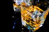 Close-up of top of view of glass of whiskey on black table with reflection — Stock Photo