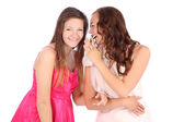 Two happy young girlfriends whispering — Foto de Stock